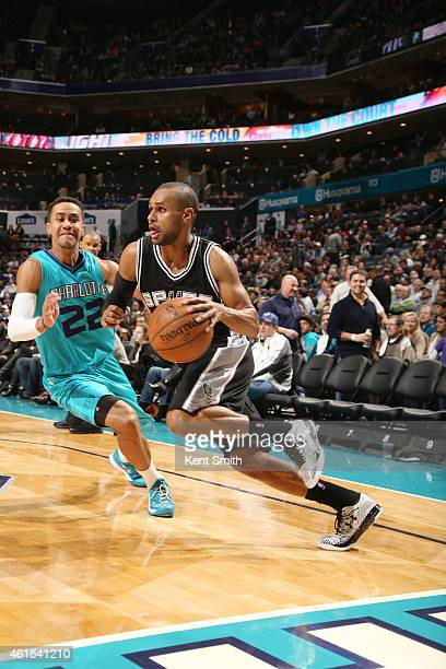 Patty Mills of the San Antonio Spurs drives against Brian Roberts of the Charlotte Hornets during the game at the Time Warner Cable Arena on January...