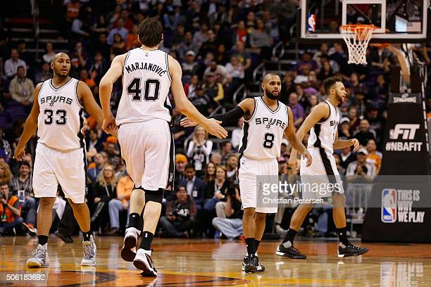 Patty Mills of the San Antonio Spurs highfives Boban Marjanovic after scoring against the Phoenix Suns during the second half of the NBA game at...