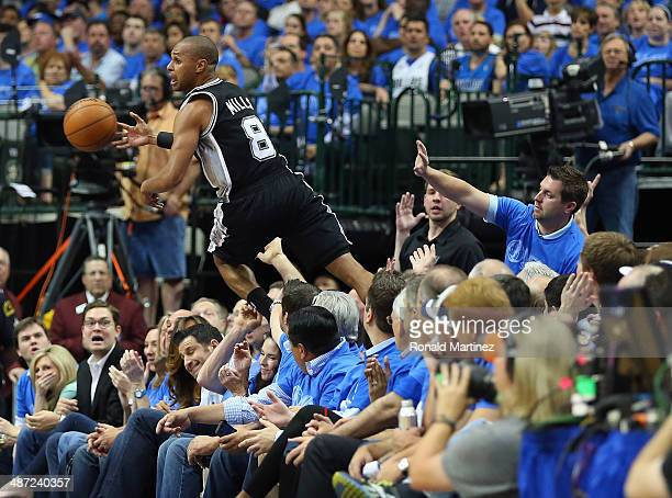 Patty Mills of the San Antonio Spurs saves the ball from falling out of bounds as he jumps over fans against the Dallas Mavericks in Game Four of the...