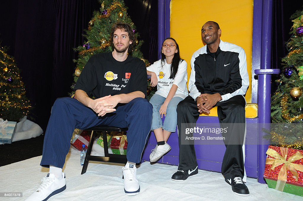 Pau Gasol #16 and <a gi-track='captionPersonalityLinkClicked' href=/galleries/search?phrase=Kobe+Bryant&family=editorial&specificpeople=201466 ng-click='$event.stopPropagation()'>Kobe Bryant</a> #24 of the Los Angeles Lakers pose for a portrait with a participant at the 2008 Los Angeles Lakers holiday party at Toyota Sports Center on December 13, 2008 in El Segundo, California.