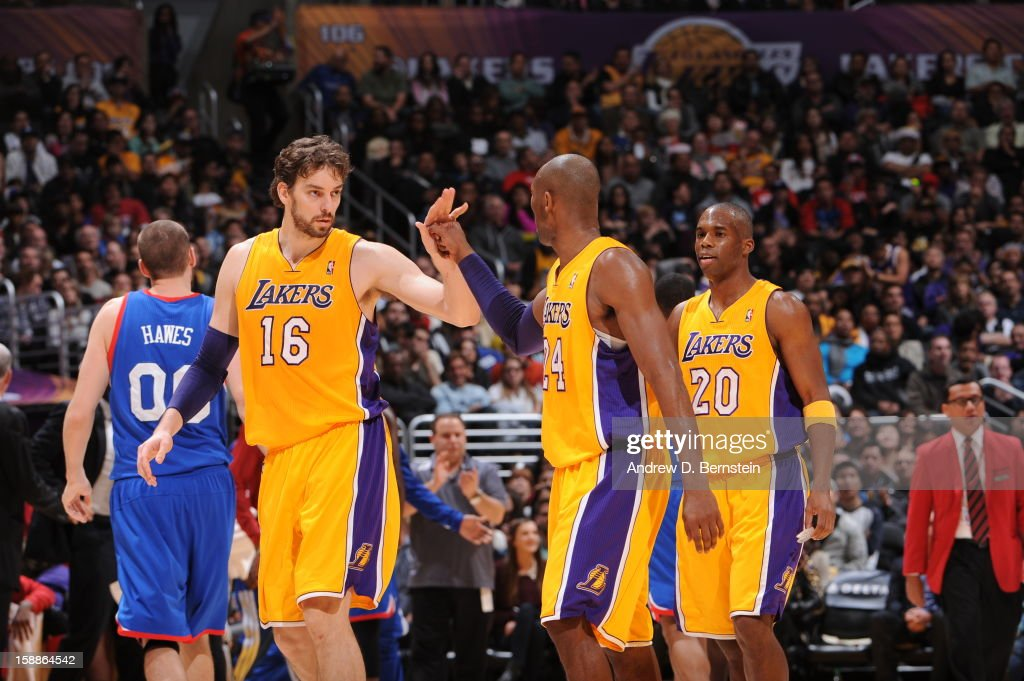 Pau Gasol #16 and Kobe Bryant #24 of the Los Angeles Lakers slap hands in their game against the Philadelphia 76ers at Staples Center on January 1, 2013 in Los Angeles, California.