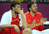 Pau Gasol of Spain and team mate and brother Marc Gasol look on from the bench in the Men's Basketball Preliminary Round match between Australia and...