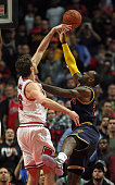 Pau Gasol of the Chicago Bulls blocks a shot by LeBron James of the Cleveland Cavaliers in the final 10 seconds during the season opening game at the...