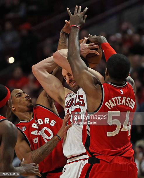 Pau Gasol of the Chicago Bulls is trapped by DeMar DeRozan and Patrick Patterson of the Toronto Raptors at the United Center on December 28 2015 in...