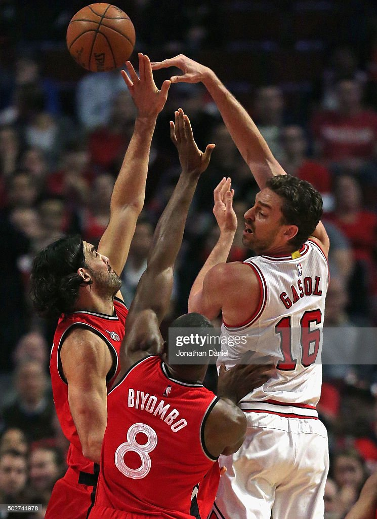Pau Gasol #16 of the Chicago Bulls passes over Luis Scola #4 and Bismack Biyombo #8 of the Toronto Raptors at the United Center on December 28, 2015 in Chicago, Illinois.