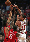 Pau Gasol of the Chicago Bulls passes over Luis Scola and Bismack Biyombo of the Toronto Raptors at the United Center on December 28 2015 in Chicago...