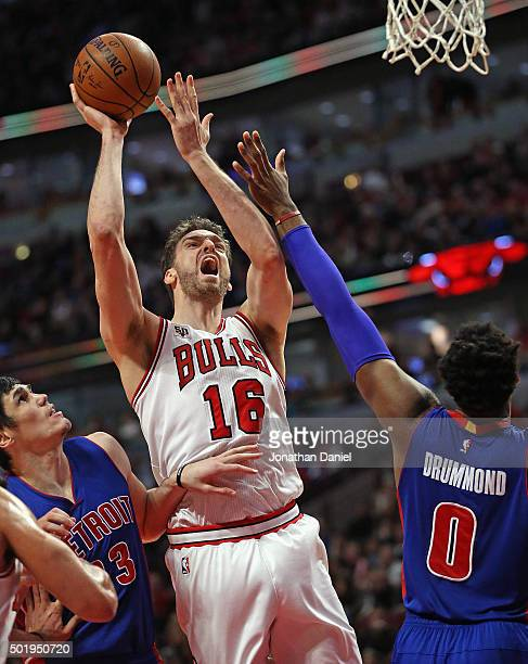 Pau Gasol of the Chicago Bulls shoots between Ersan Ilyasova and Andre Drummond of the Detroit Pistons at the United Center on December 18 2015 in...