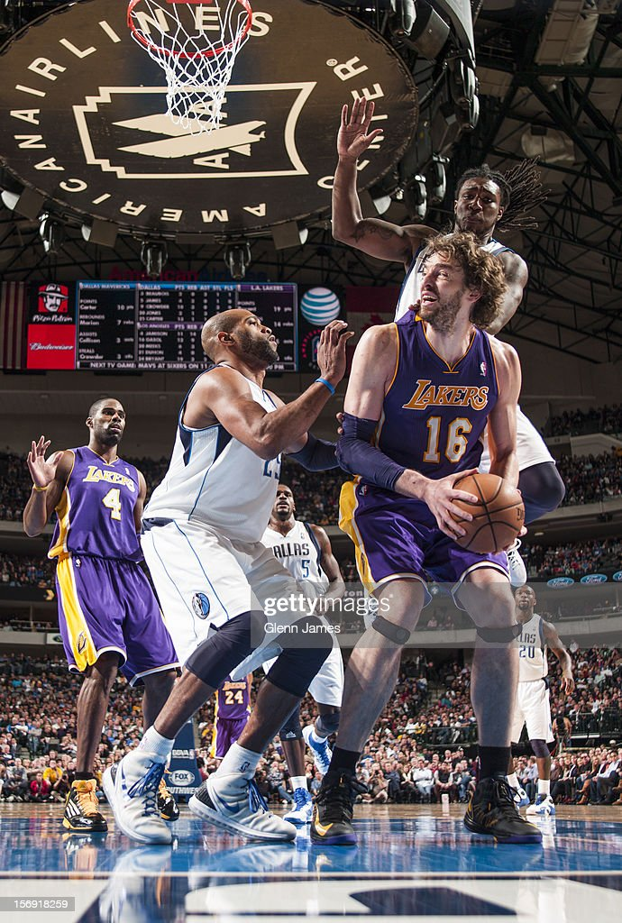 Pau Gasol #16 of the Los Angeles Lakers gets trapped underneath against Vince Carter #25 and Jae Crowder #9 of the Dallas Mavericks on November 24, 2012 at the American Airlines Center in Dallas, Texas.