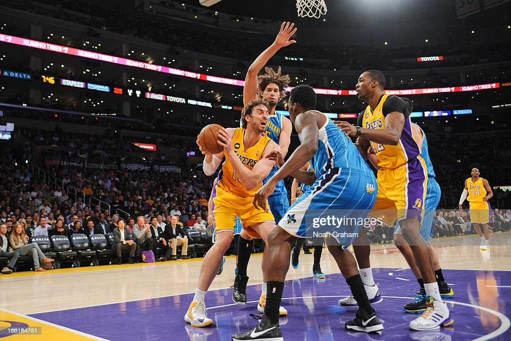 Pau Gasol #16 of the Los Angeles Lakers handles the ball in the paint against Al-Farouq Aminu #0 and Robin Lopez #15 of the New Orleans Hornets at Staples Center on April 9, 2013 in Los Angeles, California.