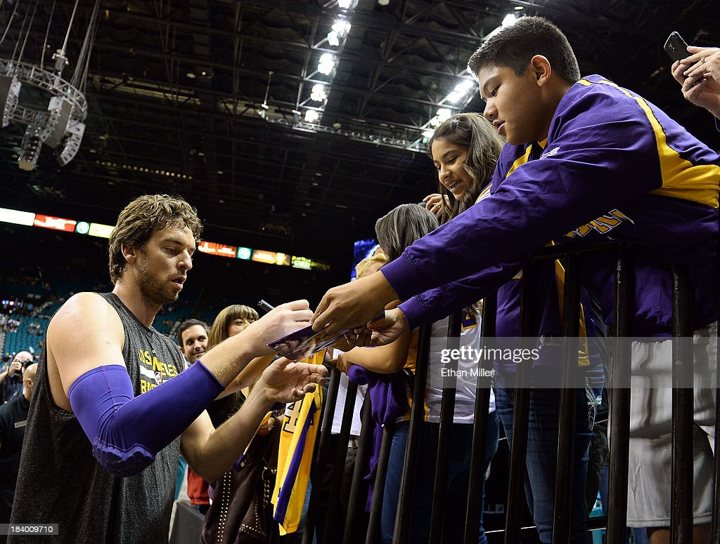 Pau Gasol #16 of the Los Angeles Lakers signs autographs for fans before a preseason game against the Sacramento Kings at the MGM Grand Garden Arena on October 10, 2013 in Las Vegas, Nevada. Sacramento won 104-86.