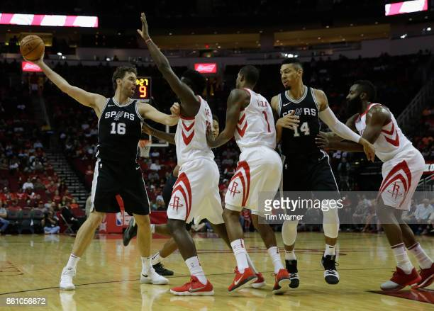Pau Gasol of the San Antonio Spurs controls the ball defended by Clint Capela of the Houston Rockets in the first half at Toyota Center on October 13...