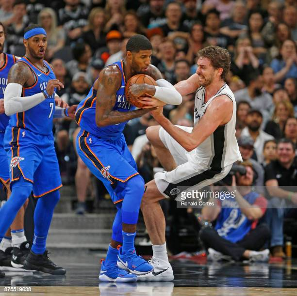 Pau Gasol of the San Antonio Spurs grapples for a loose ball with Paul George of the Oklahoma City Thunder at ATT Center on November 17 2017 in San...