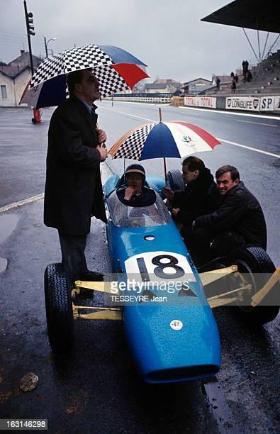 Pau Grand Prix 1964 A Pau sur le circuit René BONNET accroupi sous un parapluie parlant à son pilote Gérard LAUREAU au volant d'une voiture de...