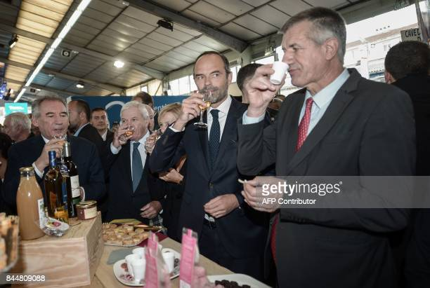 Pau mayor Francois Bayrou French Prime Minister Edouard Philippe and French lawmaker Jean Lassalle taste products from the Bearn province during the...