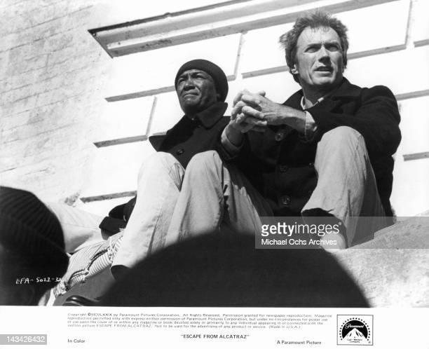 Paul Benjamin and Clint Eastwood sitting on a cement slab next to each other in a scene from the film 'Escape From Alcatraz' 1979