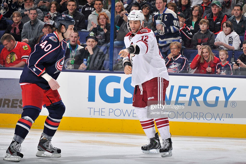 Paul Bissonnette #12 of the Phoenix Coyotes points at gloves and sticks to be cleared away before fighting with Jared Boll #40 of the Columbus Blue Jackets during the second period on March 16, 2013 at Nationwide Arena in Columbus, Ohio.