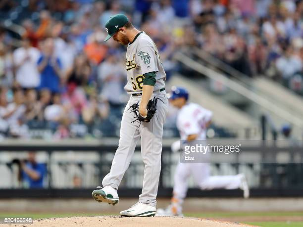 Paul Blackburn of the Oakland Athletics reacts as Michael Conforto of the New York Mets rounds third base after he hit a two run home run in the...