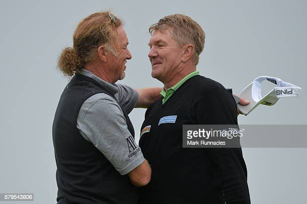 Paul Broadhurst of England is embraced by playing partner Miguel Angel Jimenez of Spain after his final putt on 18 to win The Senior Open...