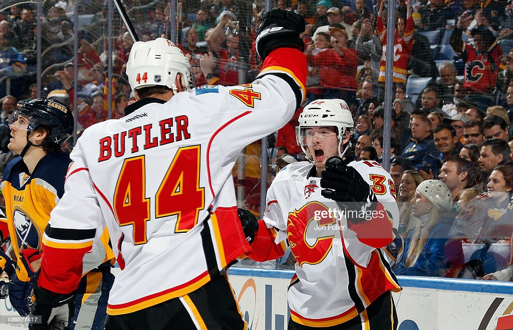 Paul Byron #32 of the Calgary Flames celebrates his third period goal against the Buffalo Sabres with teammate Chris Butler #44 at First Niagara Center on December 14, 2013 in Buffalo, New York. Calgary defeated Buffalo 2-1.