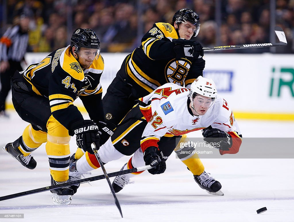 Paul Byron #32 of the Calgary Flames is hit by <a gi-track='captionPersonalityLinkClicked' href=/galleries/search?phrase=Torey+Krug&family=editorial&specificpeople=6670036 ng-click='$event.stopPropagation()'>Torey Krug</a> #47 of the Boston Bruins while chasing down a puck in front of <a gi-track='captionPersonalityLinkClicked' href=/galleries/search?phrase=Dennis+Seidenberg&family=editorial&specificpeople=204616 ng-click='$event.stopPropagation()'>Dennis Seidenberg</a> #44 of the Boston Bruins in the second period during the game at TD Garden on December 17, 2013 in Boston, Massachusetts.