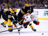 Paul Byron of the Calgary Flames is hit by Torey Krug of the Boston Bruins while chasing down a puck in front of Dennis Seidenberg of the Boston...