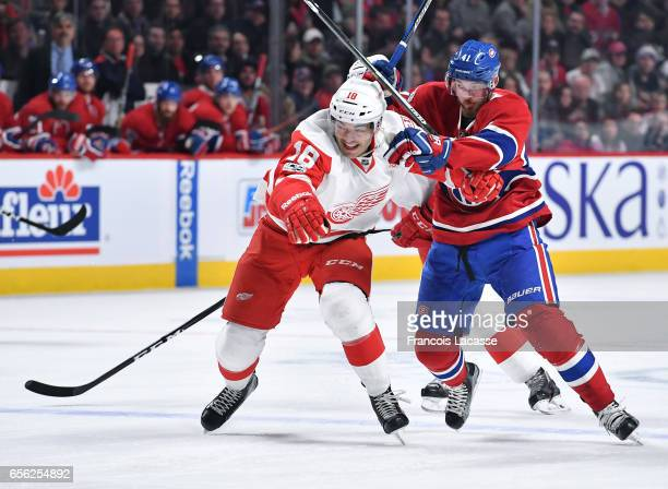 Paul Byron of the Montreal Canadiens and Robbie Russo of the Detroit Red Wings battle for position in the NHL game at the Bell Centre on March 21...