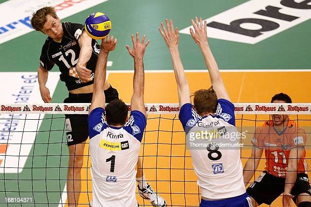 Paul Caroll of Berlin spikes the ball over Jose Rivera and Max Guenthoer of Friedrichshafen during game four of the Bundesliga Final Play Off matches...