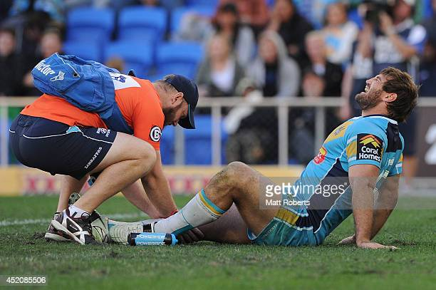 Paul Carter of the Titans receives attention from trainer Dan Ferris during the round 18 NRL match between the Gold Coast Titans and the Canberra...