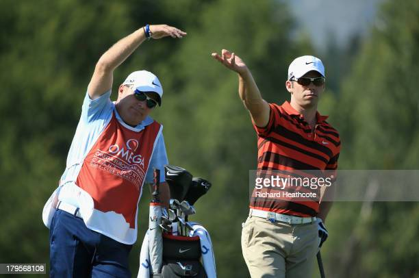 Paul Casey of England and his caddy Dominic Bott signal to the group in front during the first round of the Omega European Masters at the...