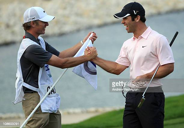 Paul Casey of England celebrates with his caddie Christian Donald on the 18th green after winning the Volvo Golf Champions at The Royal Golf Club on...