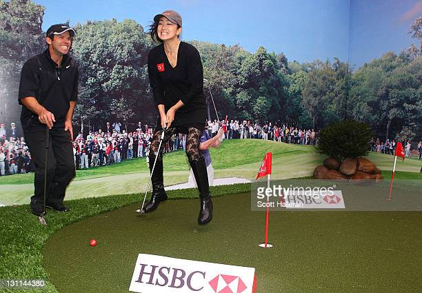 Paul Casey of England gives a putting lesson to actress Gong Li of China prior to the start of the WGCHSBC Champions at Sheshan International Golf...