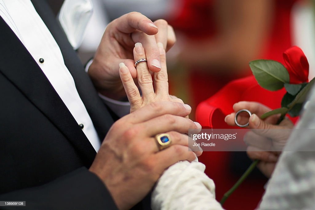 Paul Cataldo exchanges rings with Tracy Riley during a group Valentine's day wedding at the National Croquet Center on February 14 2012 in West Palm...