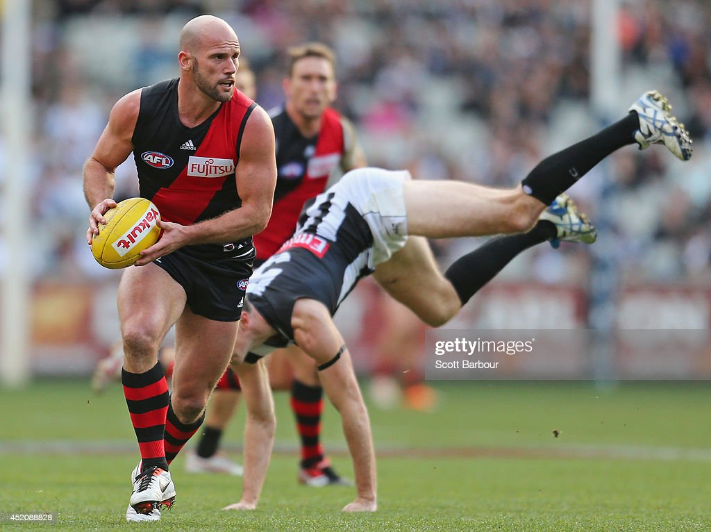 Paul Chapman of the Bombers beats the tackle of Nick Maxwell of the Magpies during the round 17 AFL match between the Essendon Bombers and the Collingwood Magpies at the Melbourne Cricket Ground on July 13, 2014 in Melbourne, Australia.