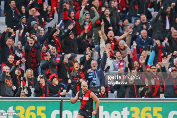 Paul Chapman of the Bombers celebrates after kicking a goal as Bombers supporters in the crowd cheer during the round 17 AFL match between the...
