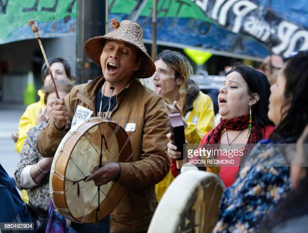 Paul Cheoketen Wagner and Chelalakem Bond sing as indigenous leaders and climate activists disrupt business at a Chase Bank branch to protest funding...
