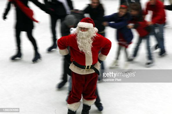 Paul Chernosky dressed as Santa Claus skates and entertains adults and children at the ice skating rink at Rockefeller Center December 20 2011 in New...