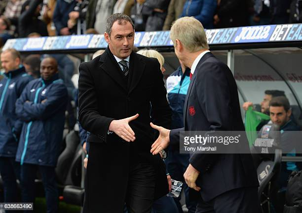 Paul Clement Manager of Swansea City shakes hands with Arsene Wenger Manager of Arsenal during the Premier League match between Swansea City and...