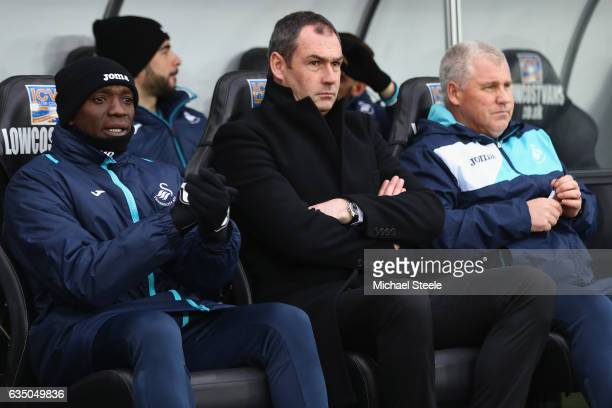Paul Clement the manager of Swansea City sits alongside coaches Nigel Gibbs and Claude Makelele during the Premier League match between Swansea City...