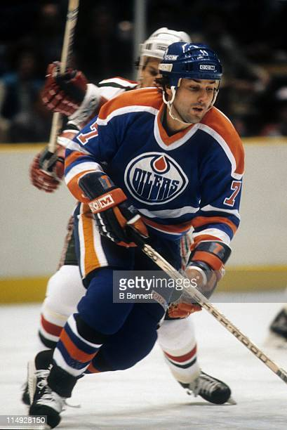 Paul Coffey of the Edmonton Oilers skates on the ice while a defender from the New Jersey Devils trails him during their game circa 1983 at the...