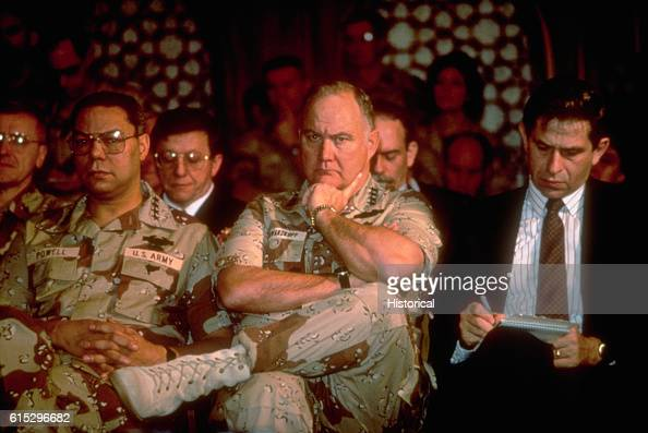 Paul D Wolfowitz under secretary of defense for policy right takes notes while General Colin Powell chairman Joint Chiefs of Staff and General Norman...