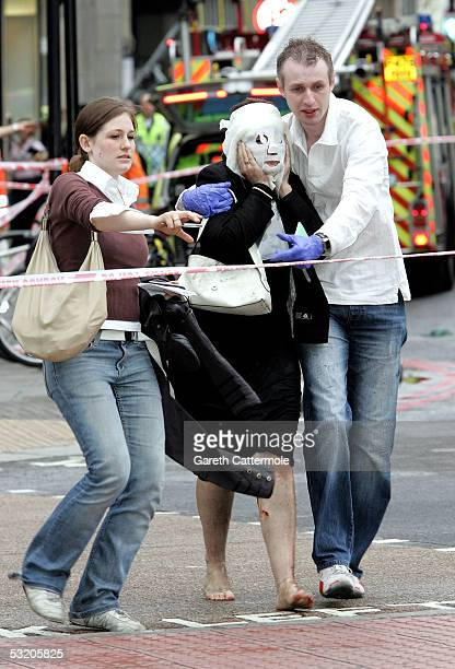Paul Dadge and an unidentified person help Davinia Turrell to safety at Edgware Road following an explosion which has ripped through London's...