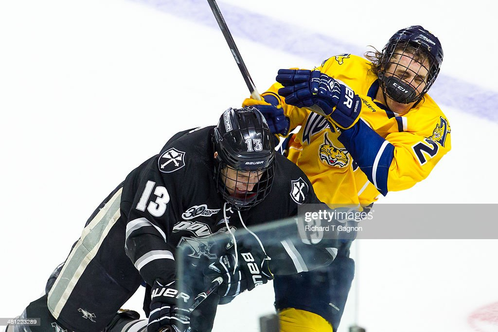 Paul de Jersey #13 of the Providence College Friars checks Brayden Sherbinin #2 of the Quinnipiac University Bobcats during the NCAA Division I Men's Ice Hockey East Regional Championship Semifinal at Webster Bank Arena on March 28, 2014 in Bridgeport, Connecticut.