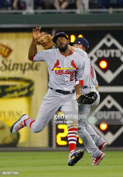 Paul DeJong of the St Louis Cardinals catches a fly ball as he collides with Dexter Fowler in the ninth inning during a game against the Philadelphia...