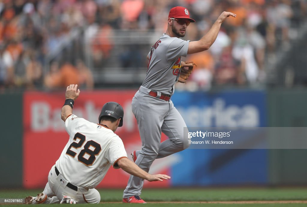 Paul DeJong #11 of the St. Louis Cardinals gets his throw off to complete the double-play over the top Buster Posey #28 of the San Francisco Giants in the bottom of the third inning at AT&T Park on September 3, 2017 in San Francisco, California.