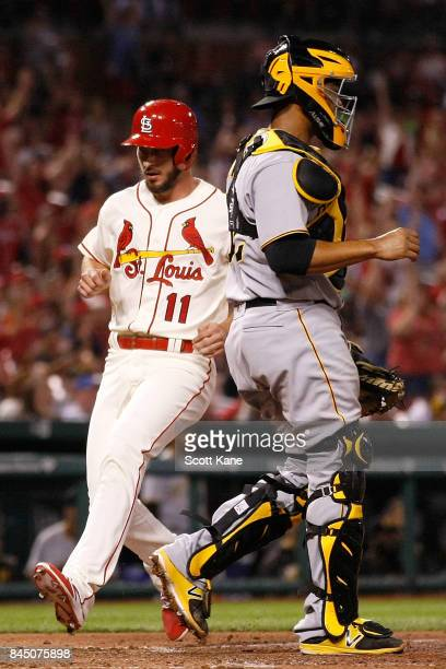 Paul DeJong of the St Louis Cardinals scores a run as Elias Diaz of the Pittsburgh Pirates stands nearby during the eighth inning at Busch Stadium on...
