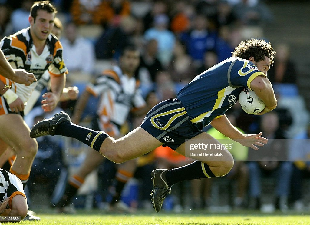 Paul Dezolt #9 of the Cowboys flies through a tackle during the round 25 NRL match between the Wests Tigers and the North Queensland Cowboys at Campbelltown Oval August 31, 2003 in Sydney, Australia.