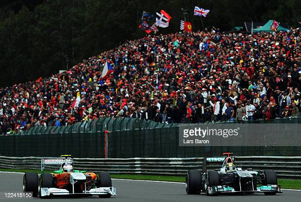 Paul di Resta of Great Britain and Force India and Michael Schumacher of Germany and Mercedes GP drive side by side during the Belgian Formula One...