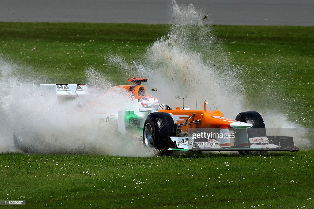 Paul di Resta of Great Britain and Force India goes through a large puddle as he drives off course during the British Grand Prix at Silverstone Circuit on July 8, 2012 in Northampton, England.