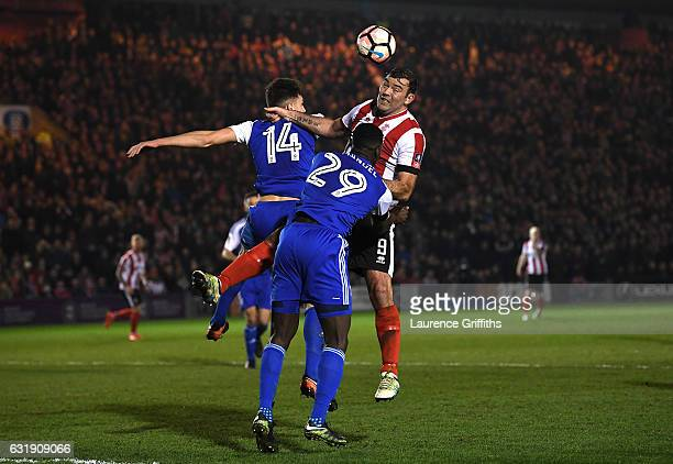 Paul Digby of Ipswich Town Josh Emmanuel of Ipswich Town and Matt Rhead of Lincoln City battle to win a header during the Emirates FA Cup third round...