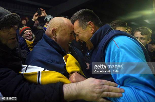 Paul Doswell manager of Sutton United celebrates with the fans after they win The Emirates FA Cup Third Round Replay match between AFC Wimbledon and...